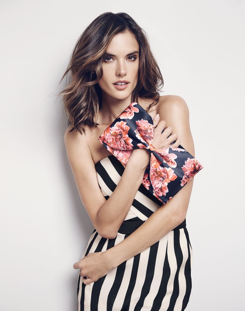 Holding on to a floral print clutch, Alessandra Ambrosio models a striped dress from Coast