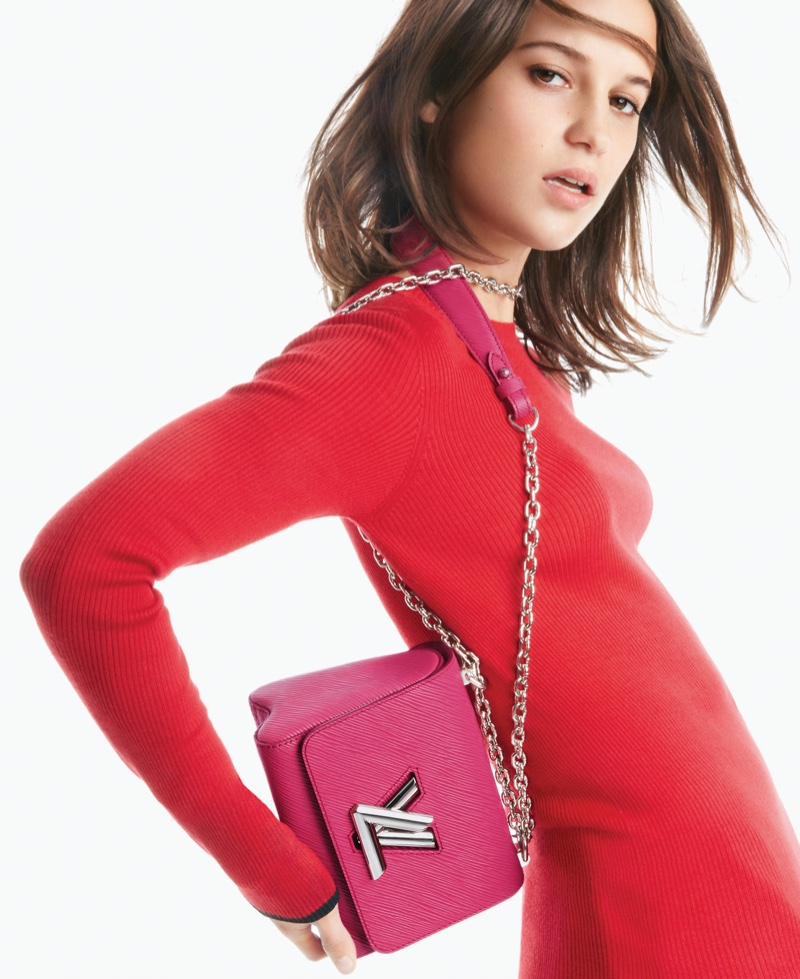 Photographed for Louis Vuitton's Twist handbag campaign, Alicia Vikander models a long sleeve sweater and the Twist bag in pink