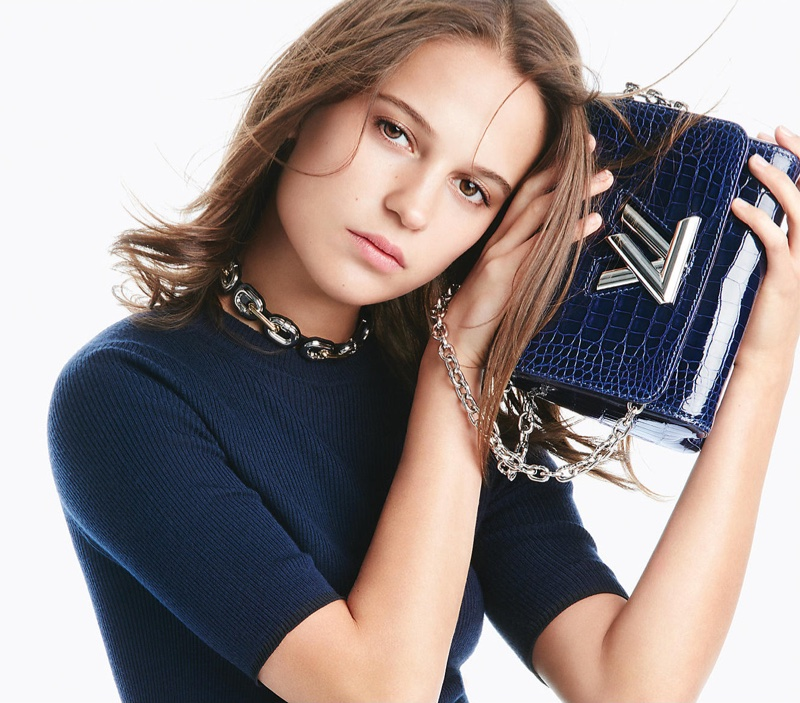 Alicia Vikander poses with Louis Vuitton's Twist bag with a knitwear top