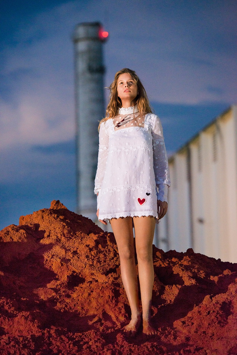 Anna Ewers poses outdoors in a high neckline white dress with long sleeves and hearts