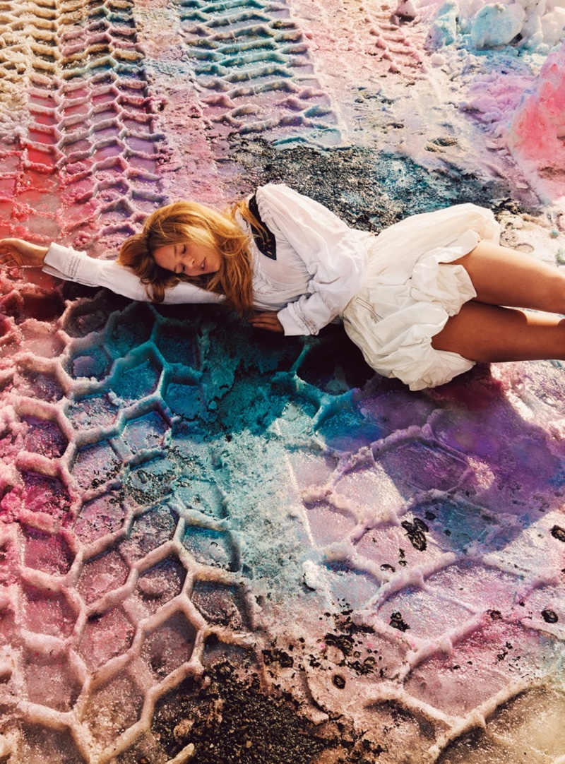 Posing with tire tracks, Anna models a white Louis Vuitton top and mini skirt