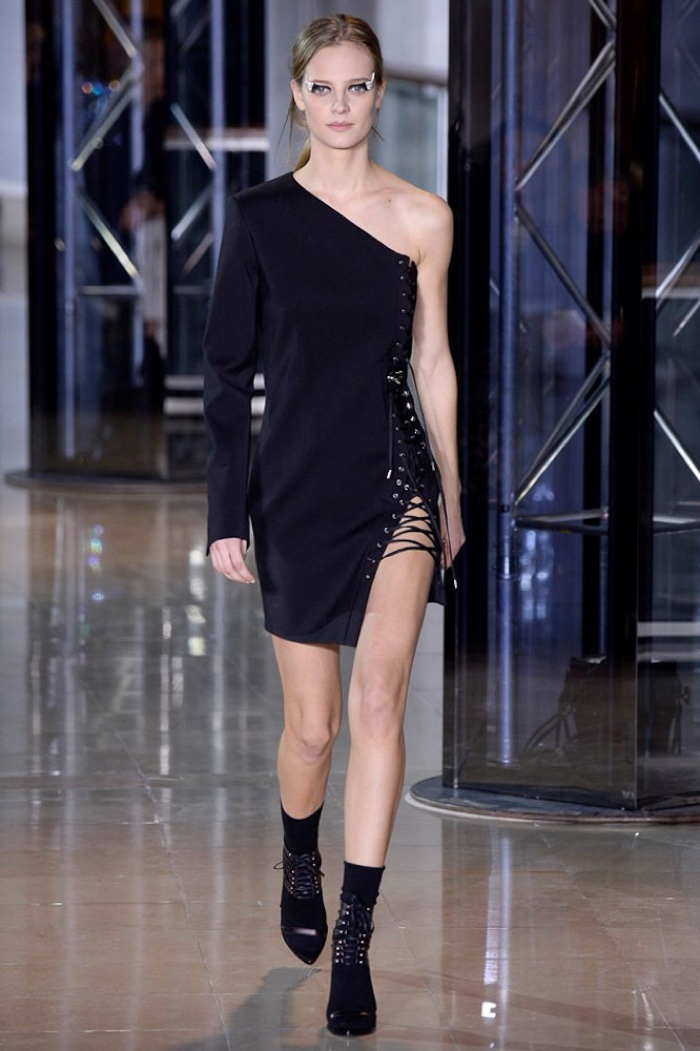 A model walks the runway at Anthony Vaccarello's fall-winter 2016 show wearing a one-shoulder dress with lace-up details at the side