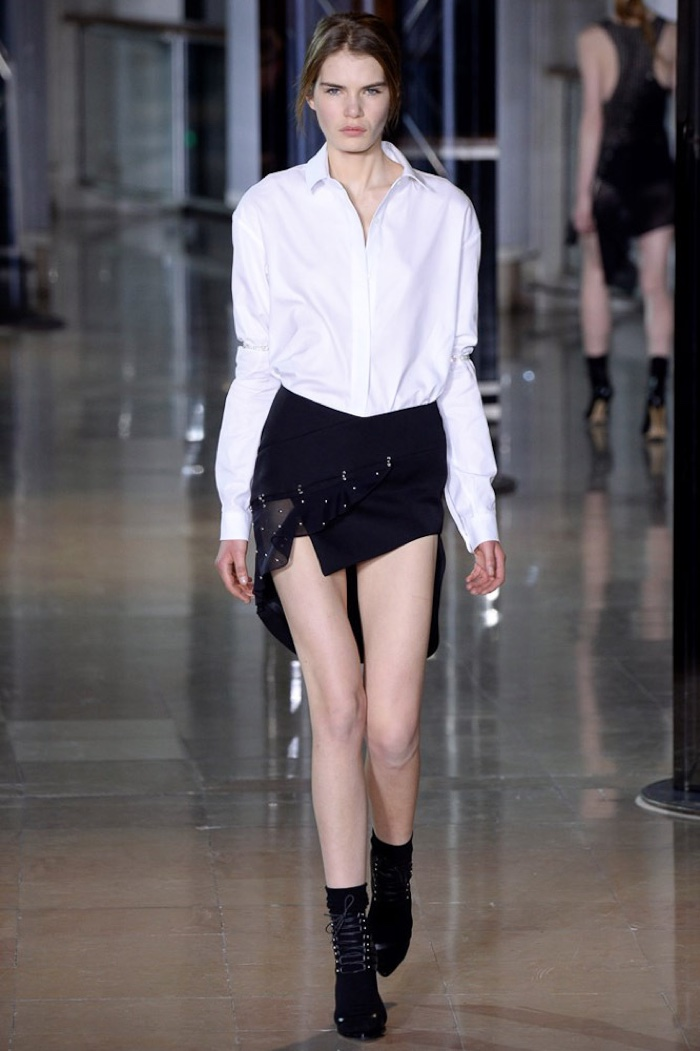 A model walks the runway at Anthony Vaccarello's fall-winter 2016 show wearing a white shirt with a black asymmetrical skirt