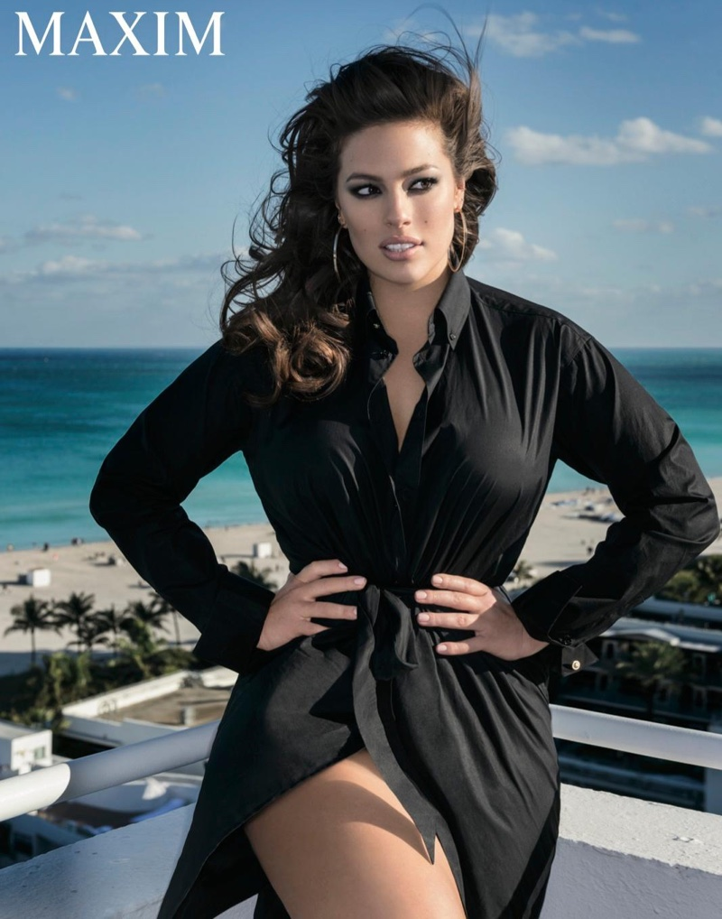 Ashley Graham poses with her hands on her waist in a black dress shirt