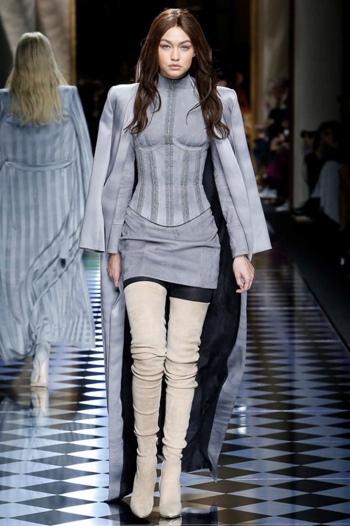 Gigi Hadid walks the runway at Balmain's fall-winter 2016 show wearing a brunette wig with a body-con dress, suede coat and thigh-high boots.