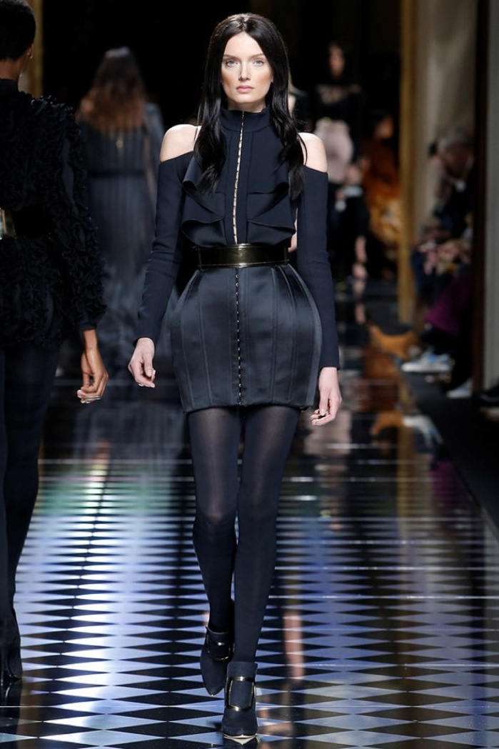 Lily Donaldson walks the runway at Balmain's fall-winter 2016 show wearing a black mini dress with cut-out shoulders