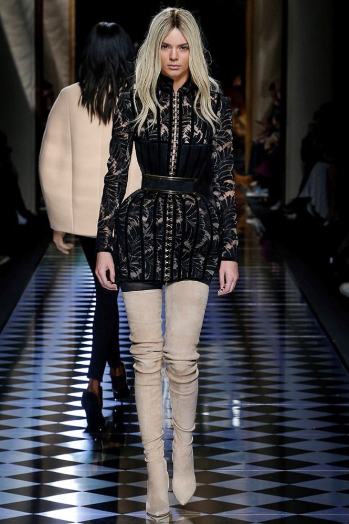 Kendall Jenner walks the runway at Balmain's fall-winter 2016 show wearing a black lace dress with padded hips and thigh-high suede boots