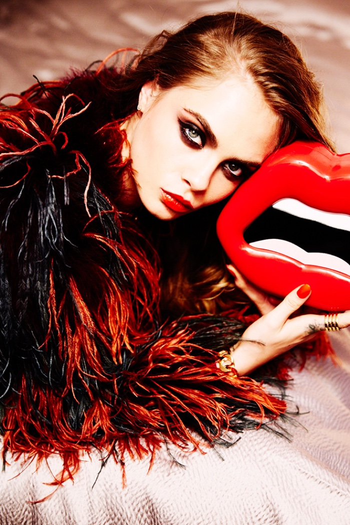 Rocking a fur coat and mouth-shaped bag, Cara Delevingne models smokey eyeshadow and siren-red lipstick