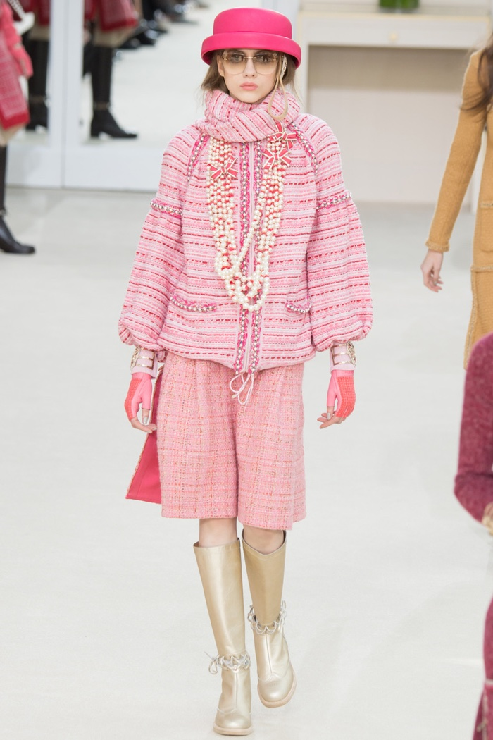 A model walks the runway at Chanel's fall-winter 2016 show wearing a pink tweed jacket and skirt with gold boots