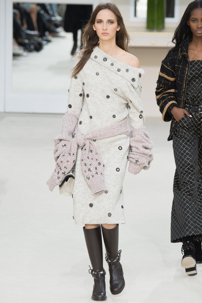 A model walks the runway at Chanel's fall-winter 2016 show wearing a sweater dress with grommets
