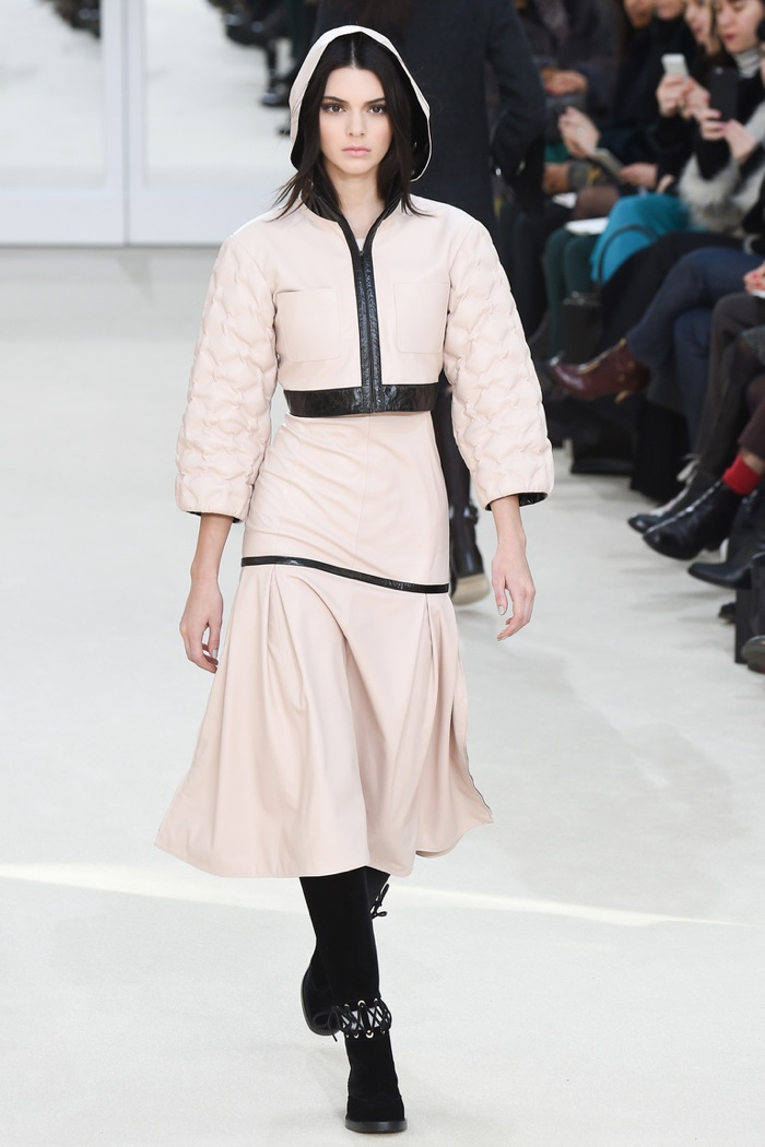 Kendall Jenner walks the runway at Chanel's fall-winter 2016 show wearing a pink hooded jacket and skirt with leather trimming