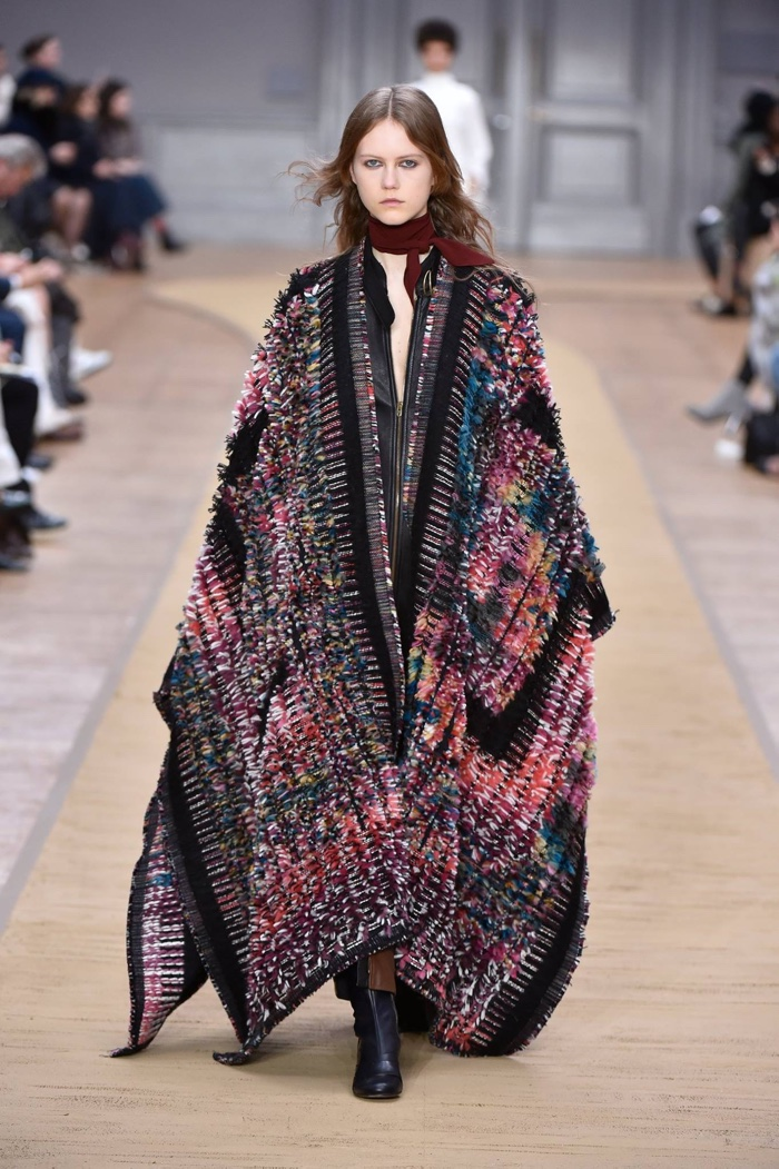 A model walks the runway at Chloe's fall-winter 2016 show wearing an embellished cape