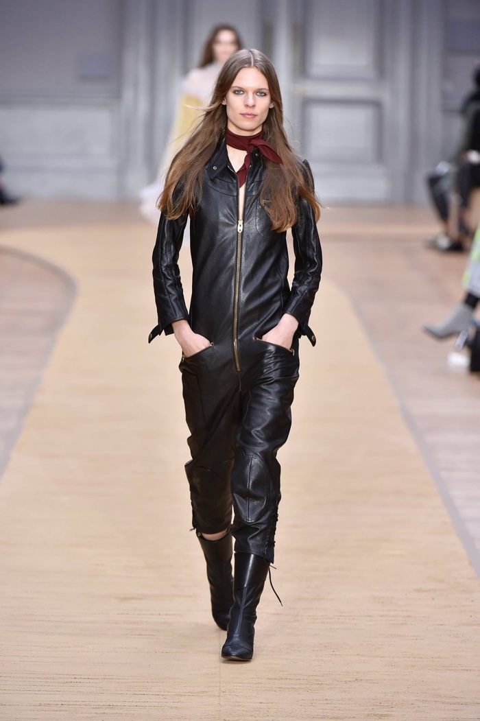 A model walks the runway at Chloe's fall-winter 2016 show wearing a leather jumpsuit and riding boots