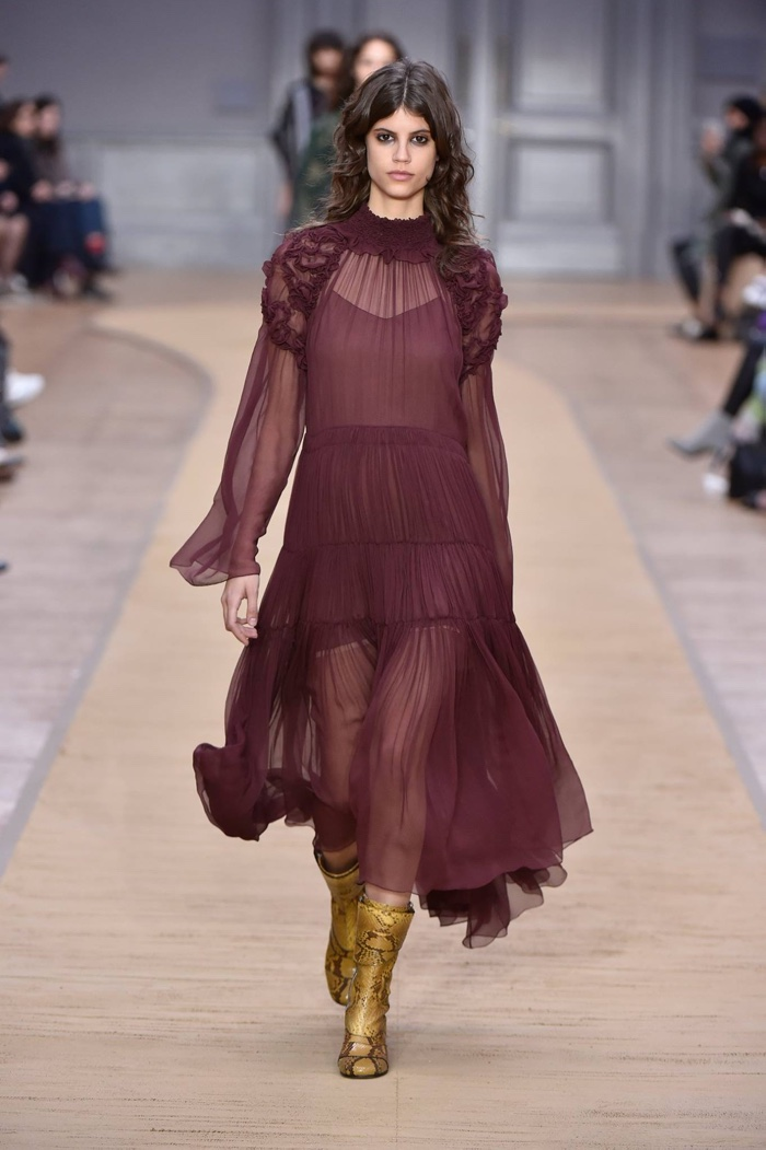 A model walks the runway at Chloe's fall-winter 2016 show wearing a burgundy dress with pleating