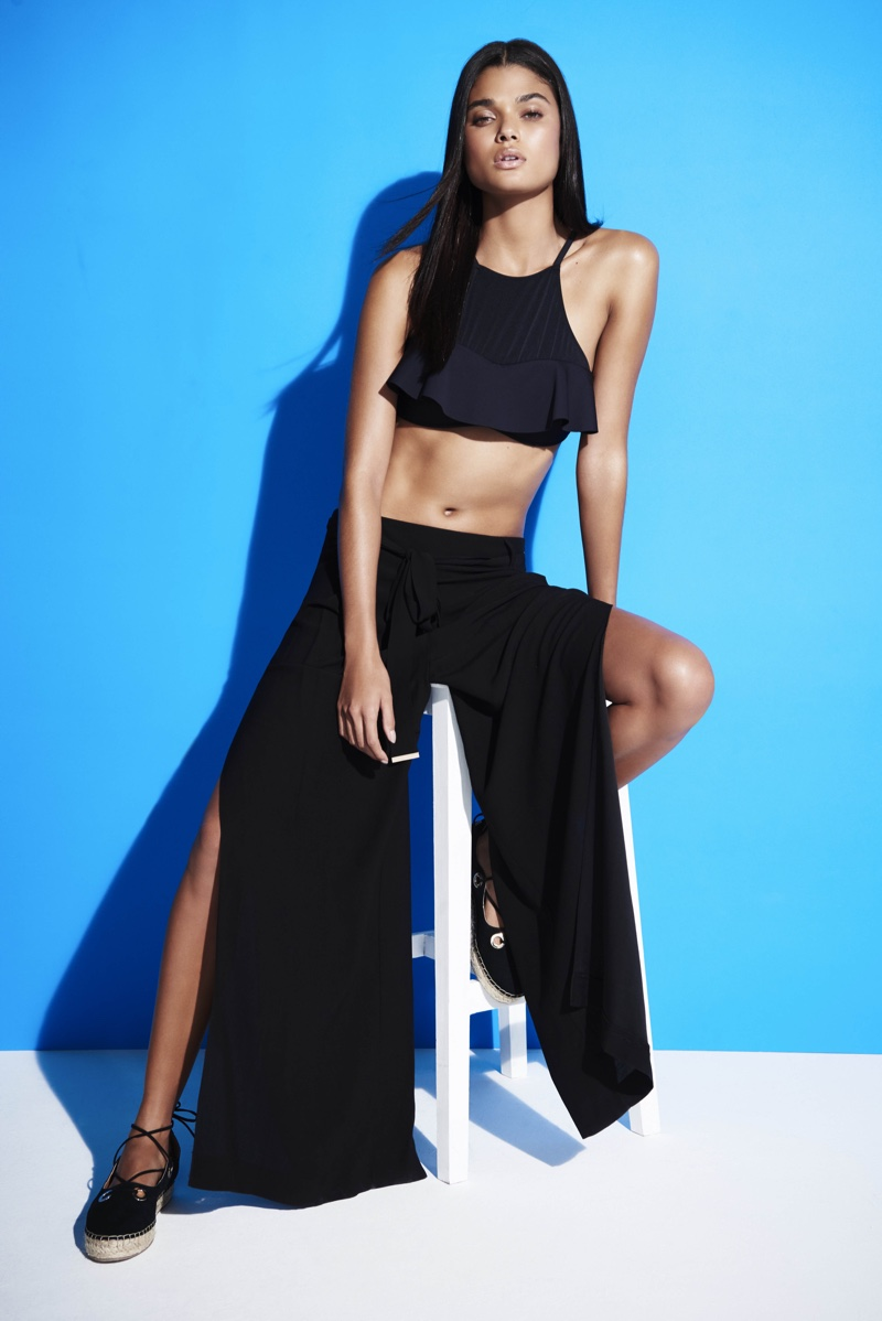 Daniela Braga sports a black crop top with wide-legged pants featuring slits