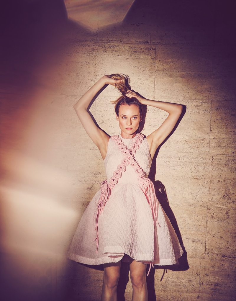 Pulling her hair into a ponytail, Diane Kruger is photographed wearing a pink Simone Rocha mini dress with an empire waist