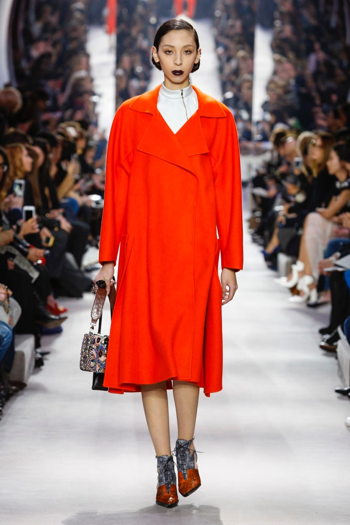 A model wears a red coat at Dior's fall-winter 2016 show