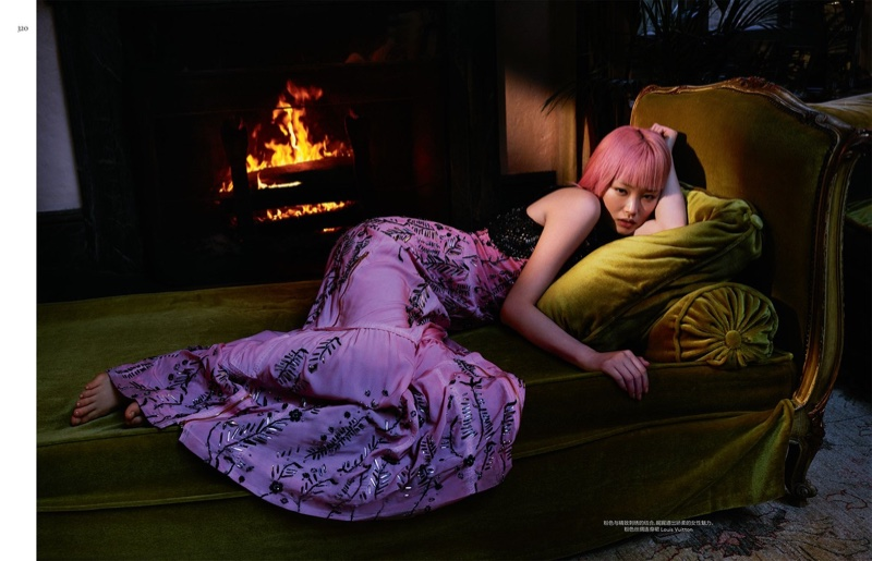 Fernanda Ly lounges near a fireplace wearing a purple Louis Vuitton dress with metallic embroideries