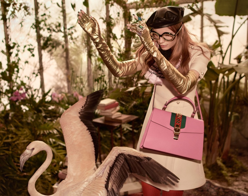 Starring in Gucci's pre-fall 2016 campaign, Polina Oganicheva poses in a wool-silk dress, gold fingerless gloves and Sylvie bag