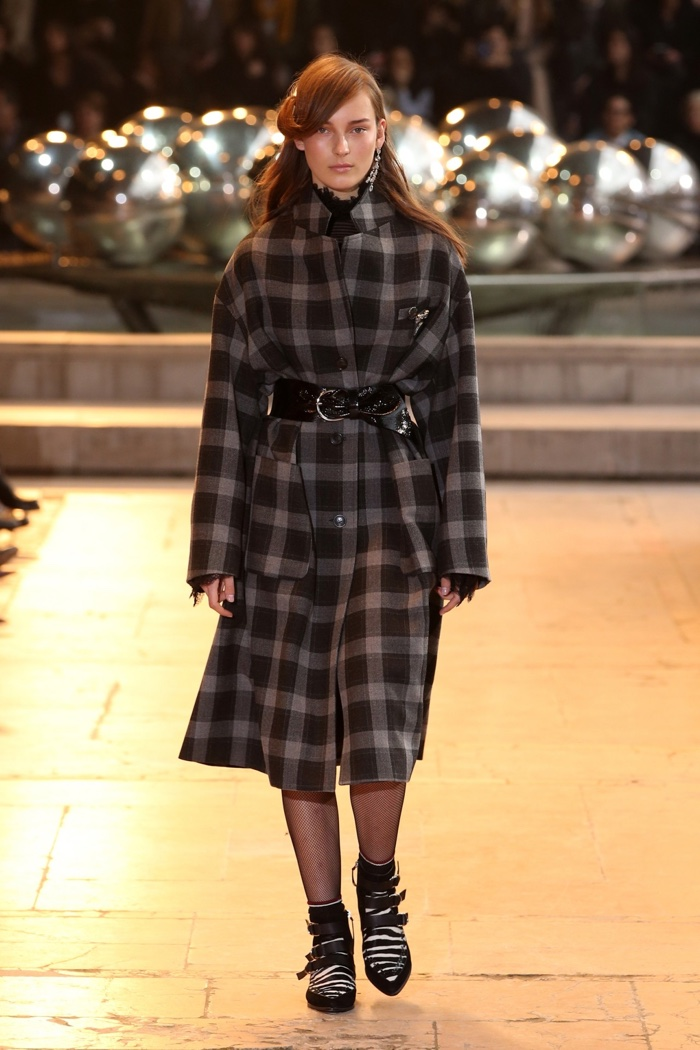 A model walks the runway at Isabel Marant's fall-winter 2016 show wearing a plaid coat
