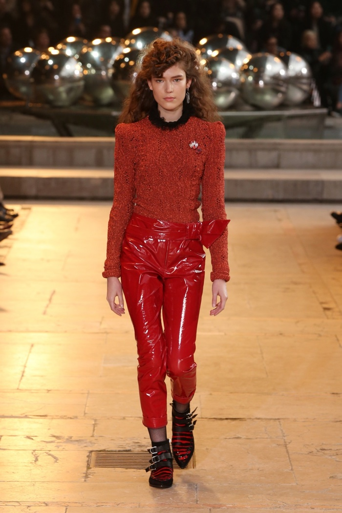 A model walks the runway at Isabel Marant's fall-winter 2016 show wearing a red sweater and patent leather pants