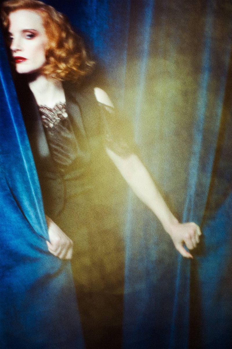 Jessica Chastain hides behind a curtain while wearing Givenchy jacket, lace top and black trousers