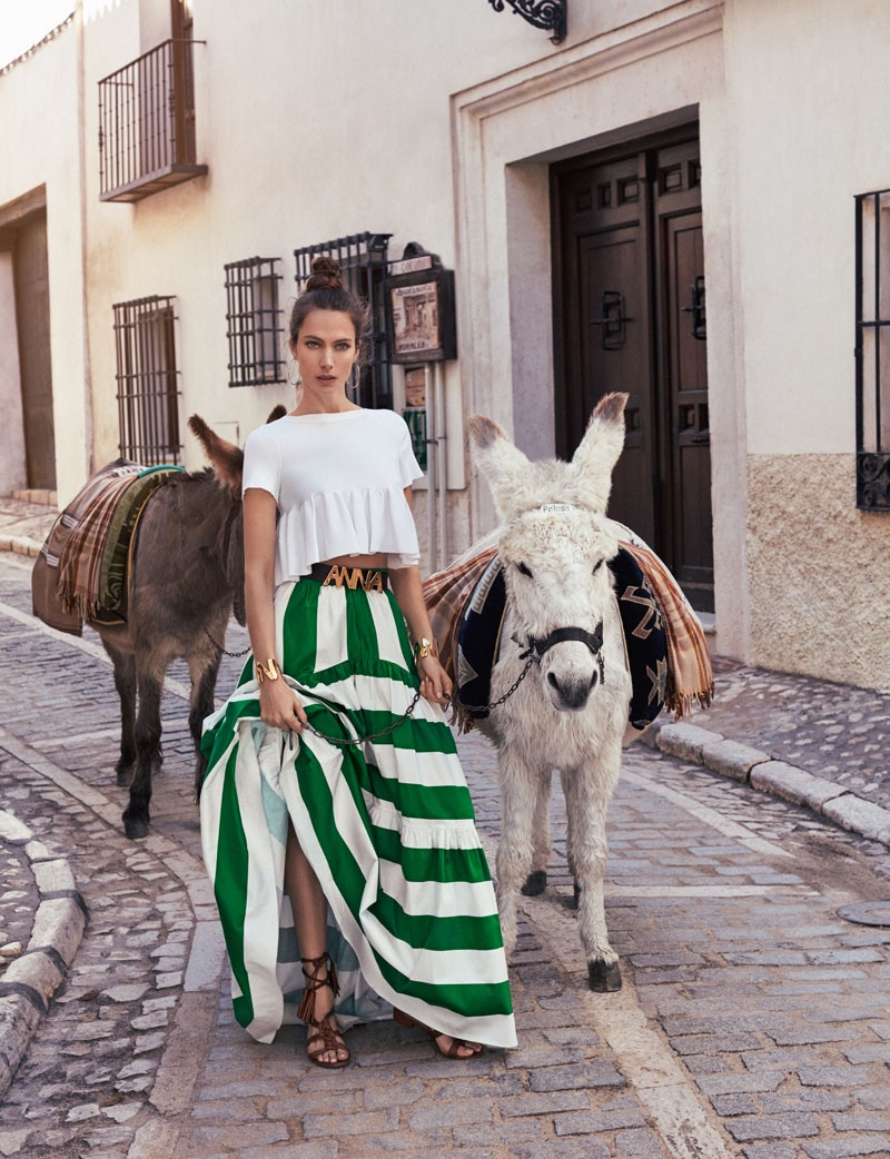 Photographed next to donkeys, the model wears a white t-shirt and green striped skirt from Blugirl