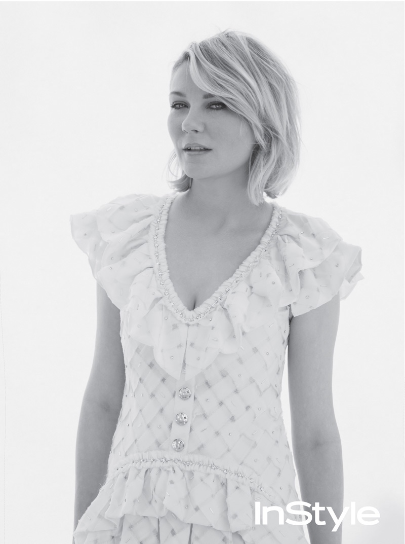 Photographed in black and white, Kirsten poses in a Chanel dress with ruffles