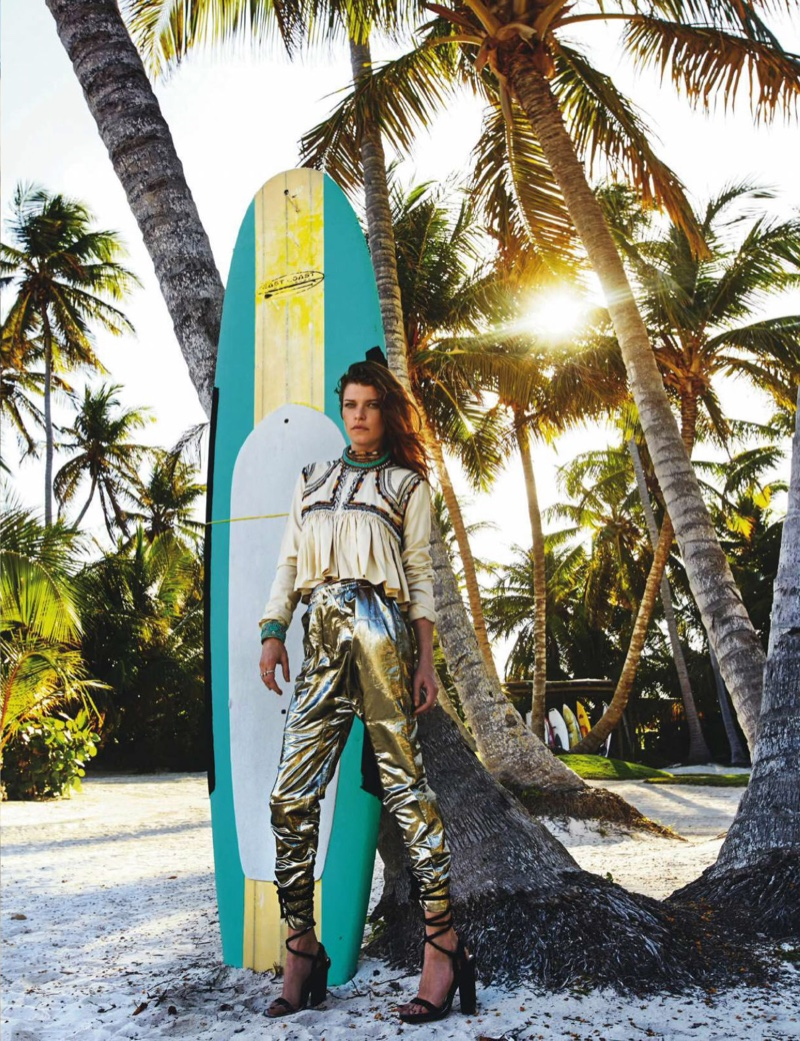 Posing next to a surf board, Louise Pedersen models an Isabel Marant top and metallic pants