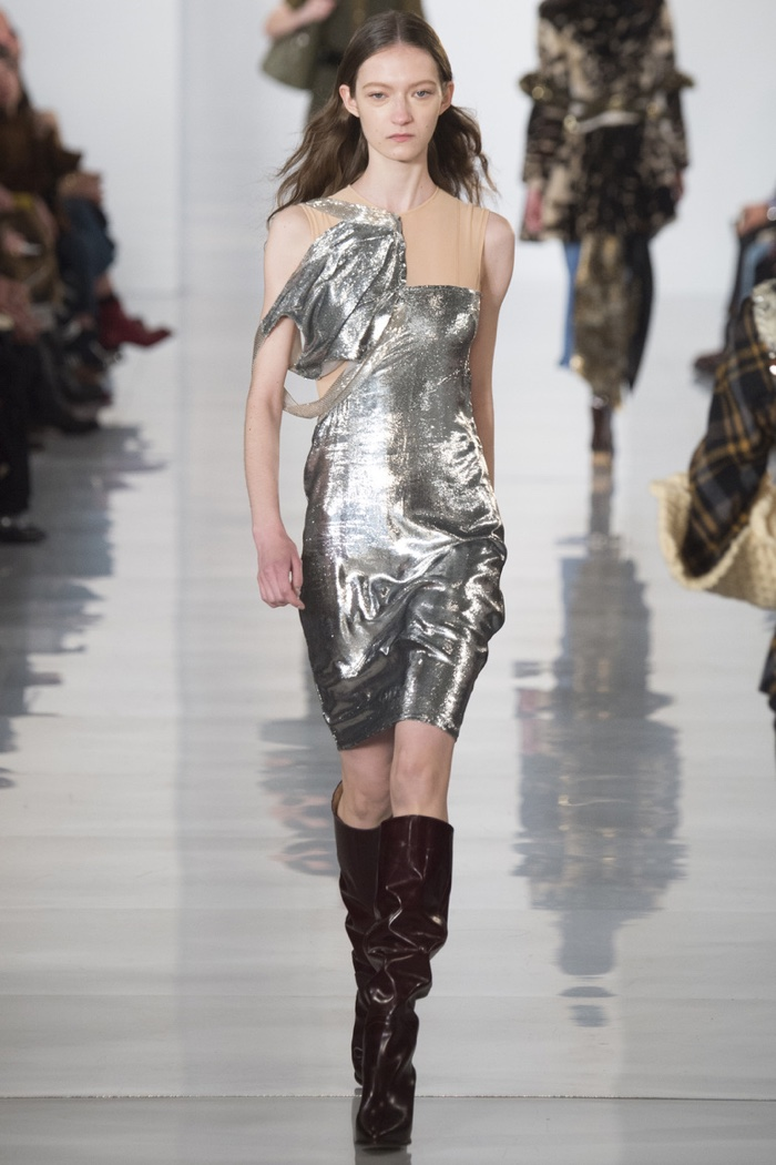 A model walks the runway at Maison Margiela's fall-winter 2016 show wearing a silver dress with knee-high boots