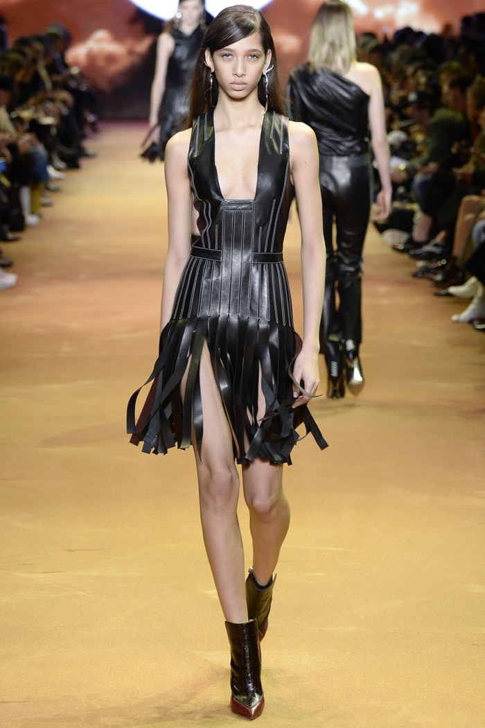 A model walks the runway at Mugler's fall-winter 2016 show wearing a leather dress with strips
