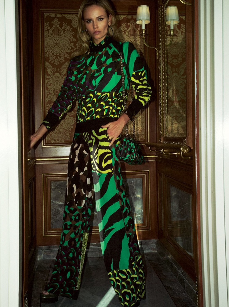 Posing near a door, Natasha Poly models a animal print cotton sweater and matching trousers designed by Versace