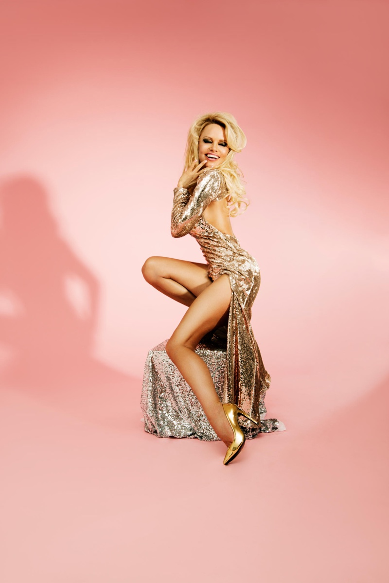 Pamela Anderson flaunts her legs in a gold dress with cut-outs to the side