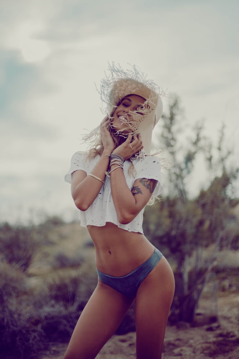Model poses in Blue Life distressed denim tee and bikini bottoms