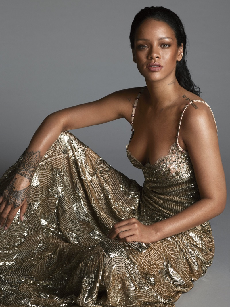 Showing off her tattoos, Rihanna poses in a gold  Givenchy Haute Couture by Riccardo Tisci gown