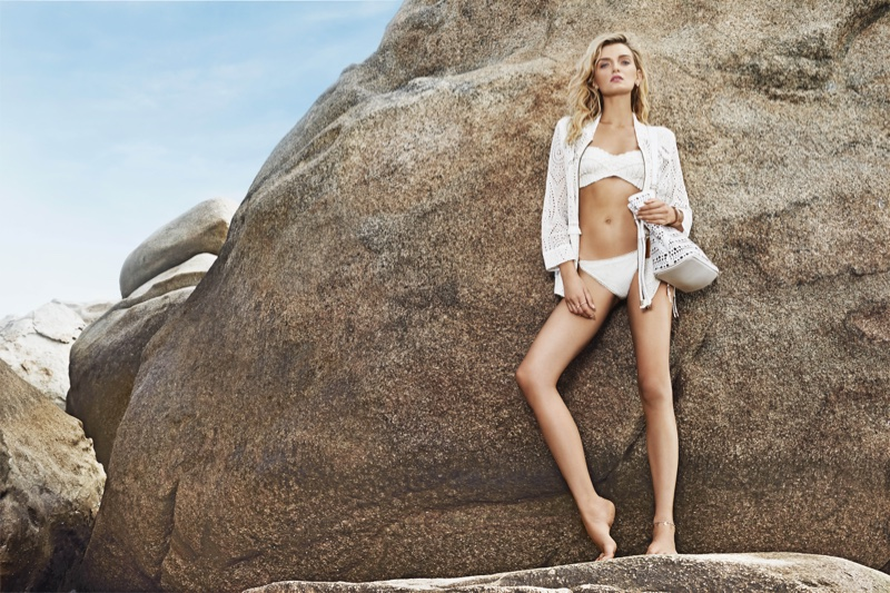 Posing at the beach, Lily models a white bikini look with coverup