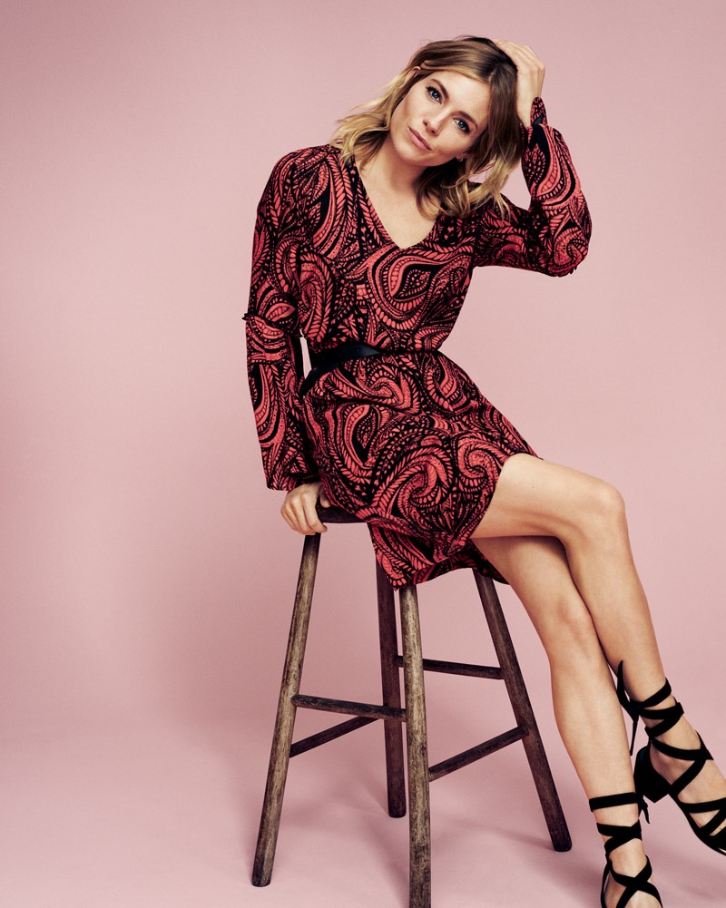 Posing on a stool, sienna Miller wears a long sleeve printed red dress from Lindex