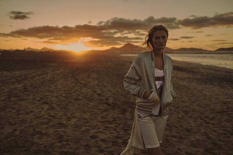 Walking the beach, Toni poses in a bomber jacket