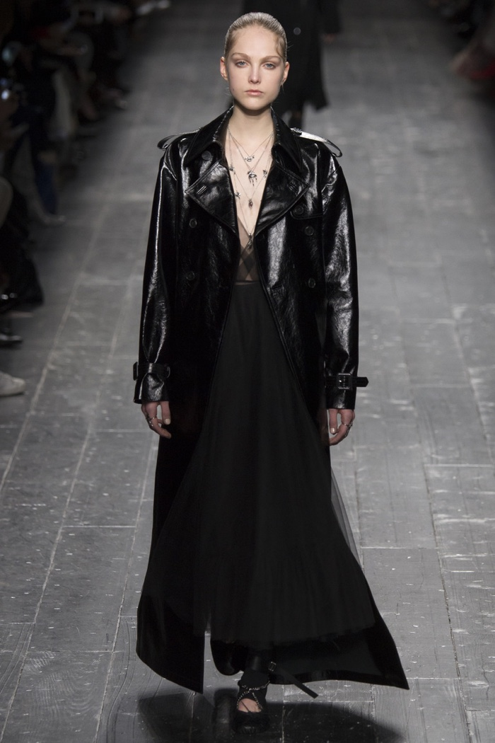 A model walks the runway at Valentino's fall-winter 2016 show wearing a black maxi dress and leather jacket