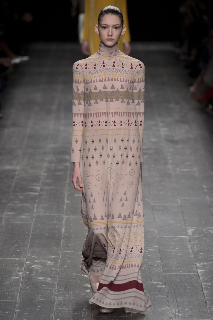 A model walks the runway at Valentino's fall-winter 2016 show wearing a long sleeve gown with prints