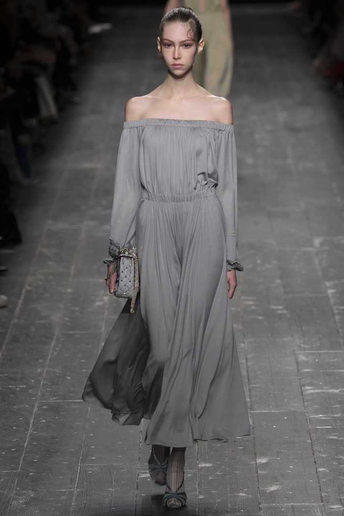 A model walks the runway at Valentino's fall-winter 2016 show wearing an off the shoulder long-sleeve gown