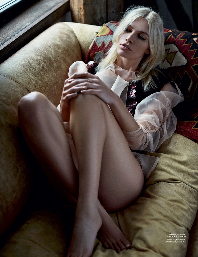 Lounging on a couch, Aline wears sheer shirt and vest look