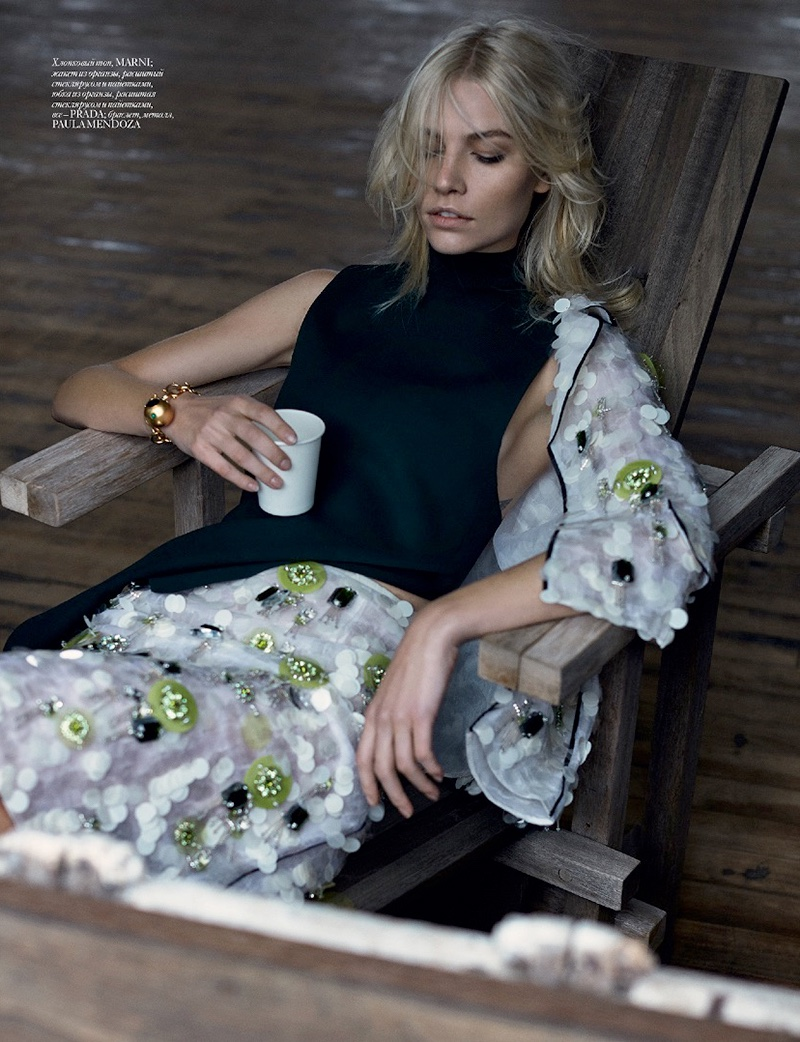 Aline sits in a lounge chair wearing Marni shirt with embellished Prada jacket and skirt