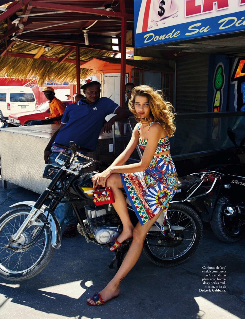 Ana Beatriz Barros poses on a motor bike in printed top and skirt with embellished sandals from Dolce & Gabbana