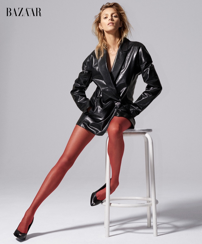 Posing on a stool, Anja Rubik models a black leather jacket designed by Anthony Vaccarello