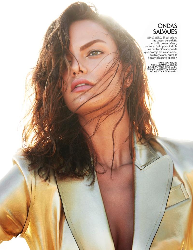 Barbara Fialho wears her hair in tousled beach waves while modeling a gold Norma Kamali jacket