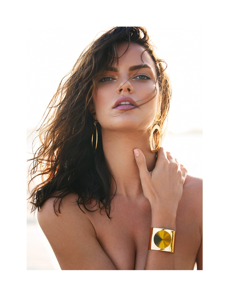 The model looks perfectly sun-kissed wearing a gold Swarovski cuff