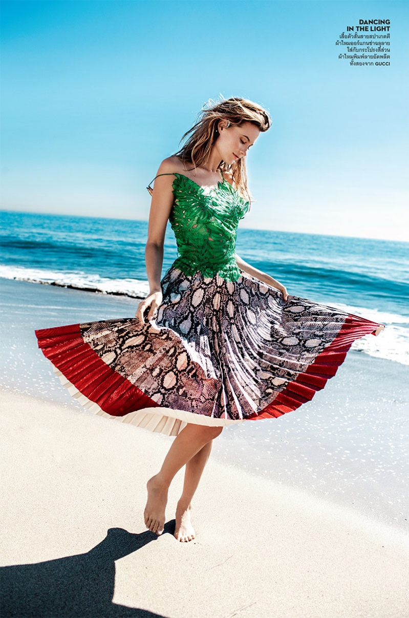Posing barefoot, Behati Prinsloo wears a Gucci top with a python print pleated skirt