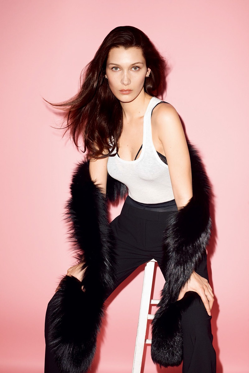 Keeping it casual glam, Bella models a white tank top and black trousers with fur stole