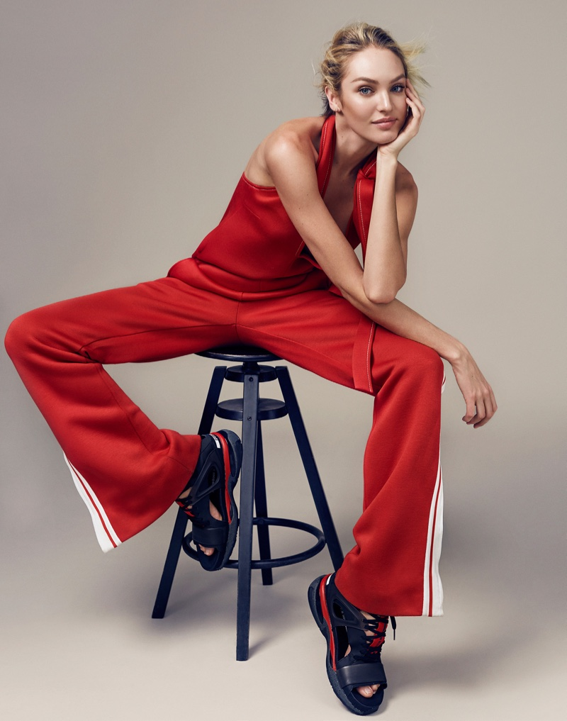 Sitting on a stool, Candice models a Chloe top and track pants in red